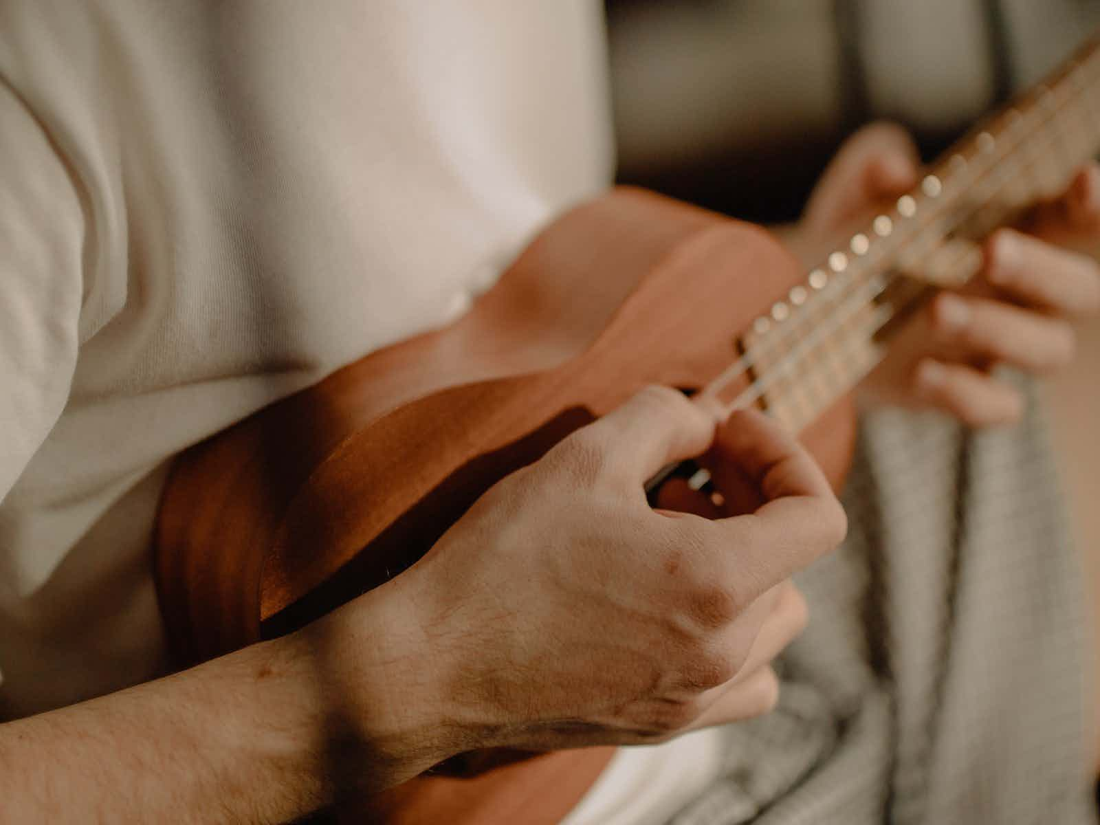 person-playing-brown-acoustic-guitar-4115010
